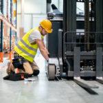 Mechanic_repairing_forklift_in_warehouse