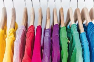 Fashion_clothes_on_clothing_rack_-_bright_colorful_closet._Closeup_of_rainbow_color_choice_of_trendy_female_wear_on_hangers_in_store_closet_or_spring_cleaning_concept._Summer_home_wardrobe.