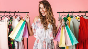 Photo_of_fashionable_girl_standing_in_store_near_clothes_rack_and_holding_colorful_shopping_bags_isolated_over_pink_background
