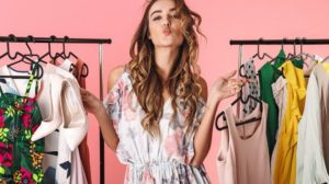 Photo_of_trendy_woman_in_dress_standing_near_wardrobe_with_clothes_and_choosing_what_to_wear_isolated_over_pink_background