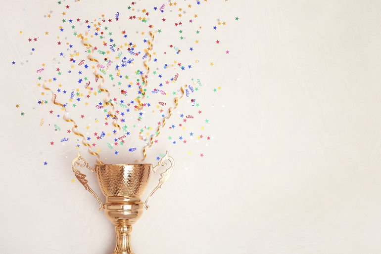 Trophy_and_confetti_on_light_background,_top_view_with_space_for_text._Victory_concept