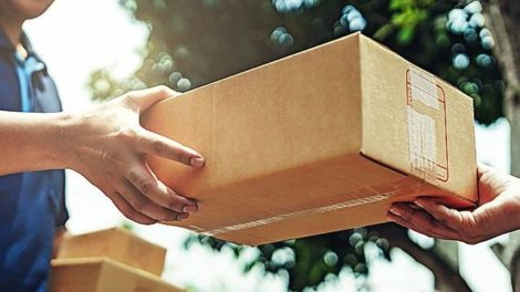 Delivery_man_delivering_holding_parcel_box_to_customer