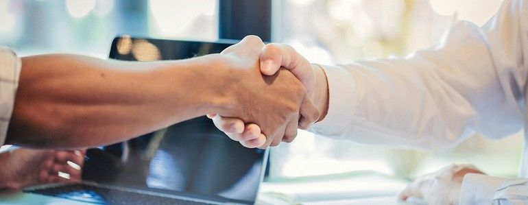 Businessman_handshake_at_business_meeting_after_negotiations_with_business_partners.
