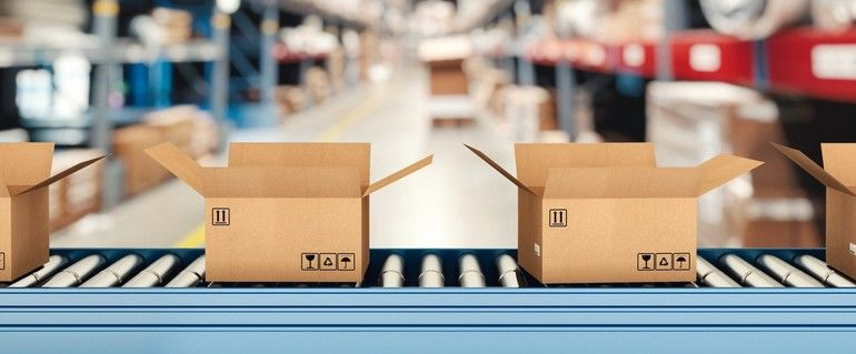 Cardboard_boxes_on_conveyor_roller_with_racks_on_background