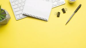 Yellow_desk_office_with_laptop,_smartphone_and_other_work_supplies_with_cup_of_coffee._Top_view_with_copy_space_for_input_the_text._Designer_workspace_on_desk_table_essential_elements_on_flat_lay.