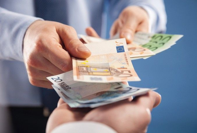 Businessman's__hands_exchanging_euro_on_blue_background,_closeup_shot