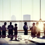 34402852_-_group_of_business_people_discussing_at_sunset_reflected_onto_table_with_documents.