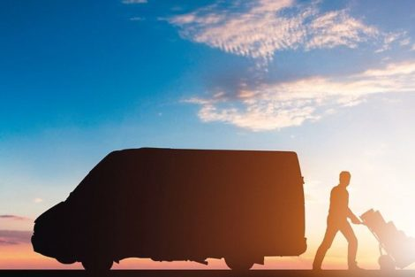 Silhouette_Of_Delivery_Courier_With_Cardboard_Boxes_On_Trolley_Near_The_Van_At_Sunset