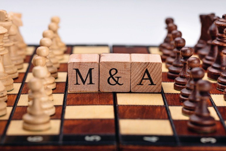 Chessboard_With_Wooden_Blocks_Showing_Mergers_And_Acquisitions_Concept