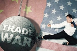 Furious_aggressive_man_wearing_business_attire_while_kicking_and_destroying_a_chained_wrecking_ball_written_Trade_War,_isolated_in_American_and_Chinese_flags_background