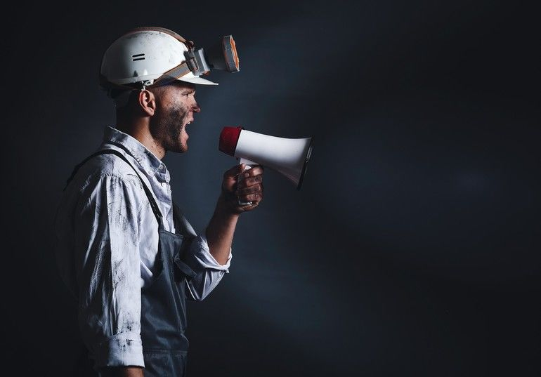 Protesting_miner_man_with_megaphone_on_dark_background