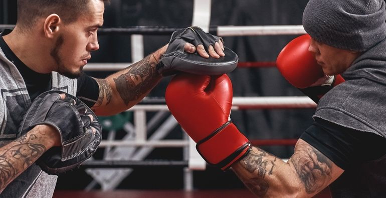 Close-up_of_confident_muscular_athlete_in_red_gloves_training_on_boxing_paws_with_partner_in_black_boxing_gym._Horizontal_photo