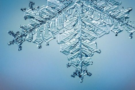Beautiful_snow_flake_on_light_blue_background_close-up