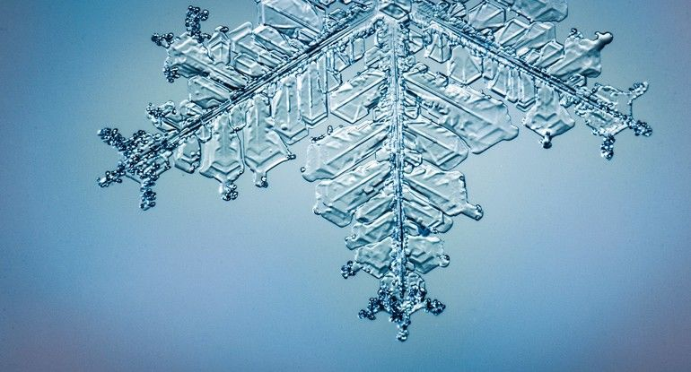 Beautiful_snow_flake_on_light_blue_background_close-up