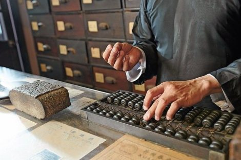 Tradiotional_Chinese_medicine_practitioner_counting_price_of_herbs_on_abacus