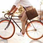 Cropped_picture_of_handsome_young_african_man_early_morning_with_bicycle_walking_outdoors.