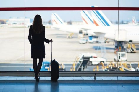 Geschäftsreisen Young_woman_in_the_airport,_looking_through_the_window_at_planes