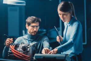 Male_and_Female_Automotive_Engineers_with_a_Tablet_Computer_and_Inspection_Tools_are_Having_a_Conversation_While_Testing_an_Electric_Engine_in_a_High_Tech_Laboratory_with_a_Concept_Car_Chassis.