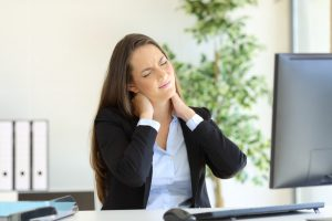 Businesswoman_suffering_neck_pain_sitting_in_a_chair_while_working_with_a_desktop_computer_in_her_workplace_at_office