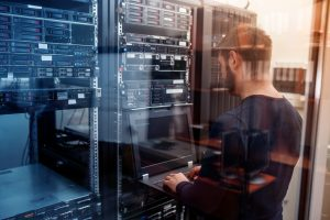 young_it_engeneer_business_man_with_thin_modern_aluminium_laptop_in_network_server_room