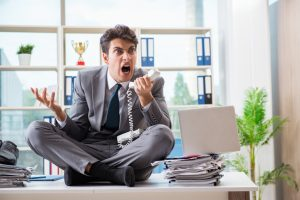 Businessman_sitting_on_top_of_desk_in_office