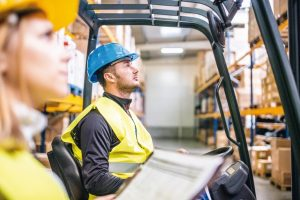 Young_workers_working_together._Man_forklift_driver_and_a_woman_in_a_warehouse.