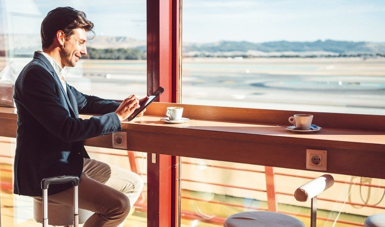 Side_view_of_handsome_young_man_using_tablet_while_drinking_coffee_in_cafe._