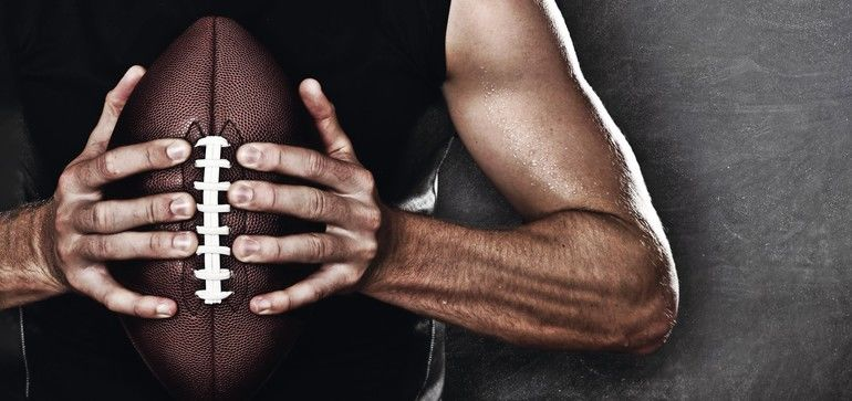 Football_player_man_player_holding_american_football_on_black_blackboard_texture_background_with_copy_space_for_text_or_design._Panoramic_banner.