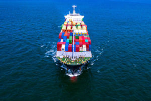 Container_cargo_ship_carrying_container_for_business_freight_import_and_export,_Aerial_view_container_ship_arriving_in_commercial_port.