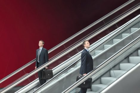 business_man_going_up_and_down_escalators,_concept_of_choice_and_success