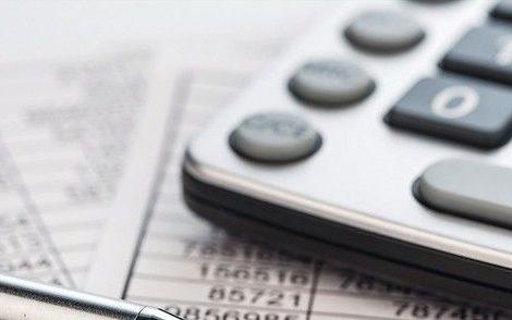 Ein_Taschenrechner_liegt_auf_den_Zahlen_einer_Bilanz_uns_Statistik._Symbolphoto_für_Umsatz,_Gewinn_und_Kosten.