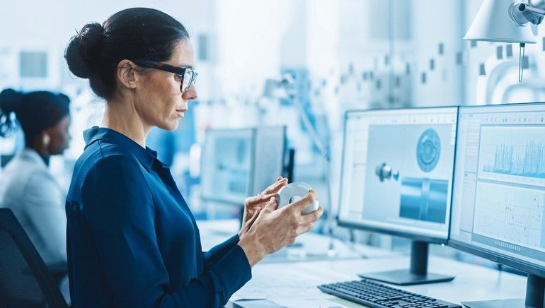 Female_Engineer_Working_on_Personal_Computer,_Inspecting_Model_of_Industrial_Machinery_Mechanism._She_Works_with_Team_of_Industrial_Professionals_in_Office_that's_Located_in_the_Working_Modern_Factory