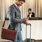 Businessman_standing_in_hotel_lobby_with_suitcase_and_using_his_mobile_phone._Male_business_traveler_in_hotel_hallway_with_smartphone_and_luggage.