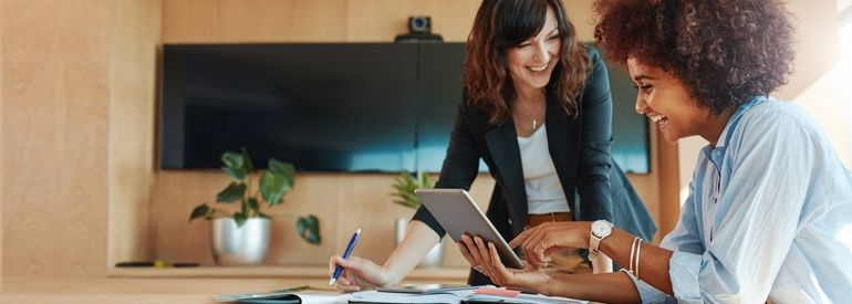 Shot_of_two_businesswoman_working_together_on_digital_tablet._Creative_female_executives_meeting_in_an_office_using_tablet_pc_and_smiling.