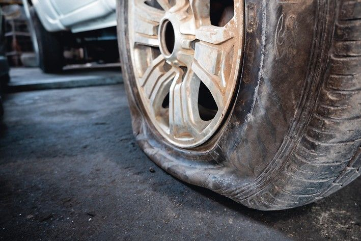 Close-up_of_a_damaged_flat_tire_of_a_car