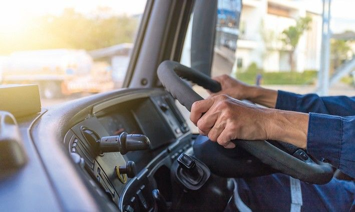 Truck_driver_keeps_driving_with_hands,The_man_Behind_Semi_Truck_Steering_Wheel.