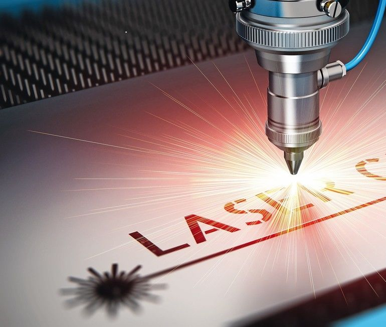 Laser_cutting_metal_industry_concept:_macro_view_of_industrial_digital_CNC_-_computer_numerical_control_CO2_invisible_laser_beam_cutter_machine_cutting_stainless_steel_sheet_with_lot_of_bright_shiny_sparkles
