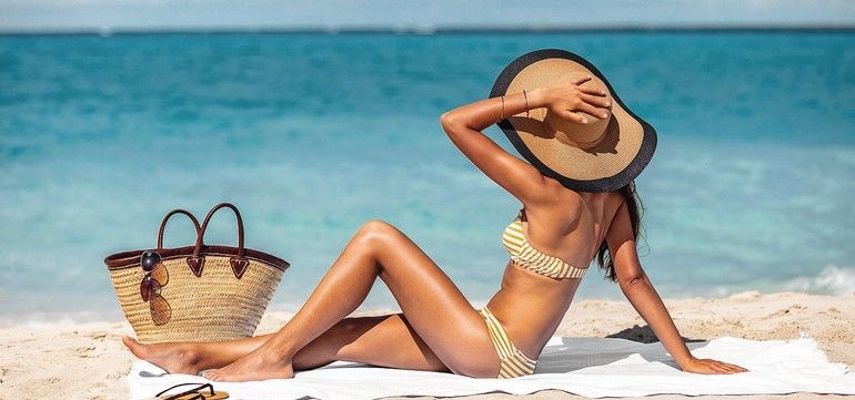 Sexy_bikini_woman_tanning_relaxing_on_beach._Suntan_concept._Unrecognizable_female_adult_from_the_back_lying_down_with_straw_hat_sunbathing_under_the_tropical_sun_on_Caribbean_vacation.