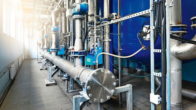 Large_industrial_water_treatment_and_boiler_room._Shiny_steel_metal_pipes_and_blue_pumps_and_valves.