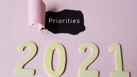 Priorities_text_on_torn_paper_with_Year_2021_background._Happy_New_Year_Concept