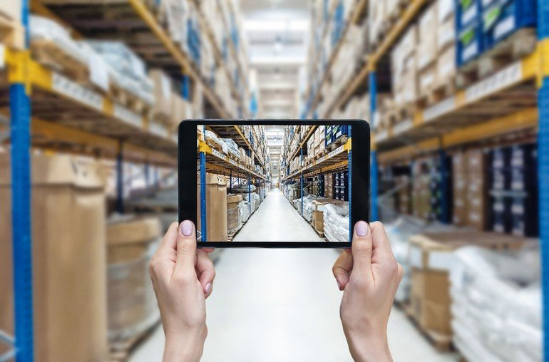 Horizontal_color_image_of_female_hands_holding_a_digital_tablet_in_a_corridor_of_futuristic_distribution_warehouse._Ordering_on-line_from_a_modern_warehouse_on_a_touchscreen_tablet_computer._Large_distribution_storage_in_background_with_racks_full_of_pack