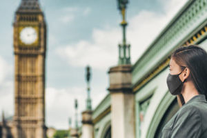 COVID-19_mask_wearing_business_people_walking_in_London_city._Asian_woman_using_face_cover_for_public_outdoor_spaces_in_urban_landscape_banner._Tourist_at_view_of_Big_Ben,_UK.