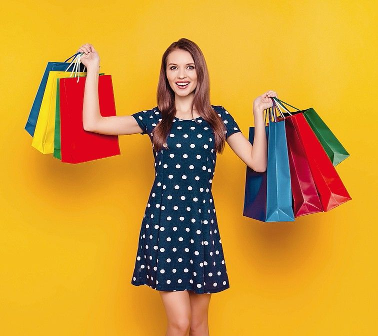 Attractive,_charming,_pretty,_happy_girl_bragging_about_purchases,_having_colorful_shopping_packets_in_two_hands,_she_bought_a_lot_of_things_and_spend_much_money,_isolated_on_yellow_background