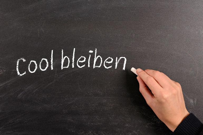 Hand_writing_German_Keep_cool_with_chalk_on_a_blackboard