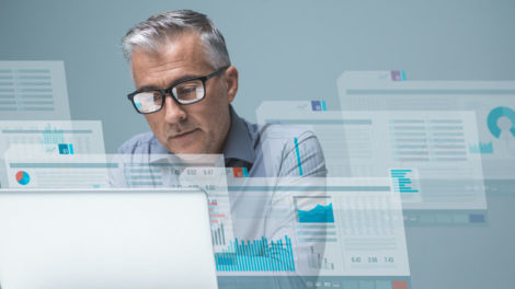 Businessman_reading_financial_reports_on_visual_screens_and_working_with_a_laptop,_finance_and_technology_concept