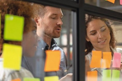 Close_up_head_shot_smiling_female_african_american_and_caucasian_colleagues_showing_working_progress_to_confident_male_team_leader_on_kanban_agile_glass_window_board_with_colorful_paper_stickers.