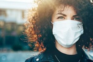 Close_up_portrait_caucasian_businesswoman_with_curly_hair_is_looking_at_camera_while_wearing_a_protective_mask