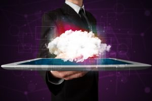 Businessman_holding_tablet_with_cloud_icon_and_purple_background