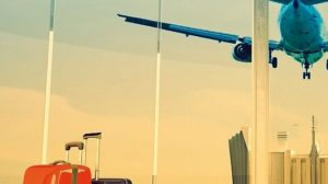 passenger_plane_flying_over_airport_terminal_-_traveling_luggage_at_airport_terminal