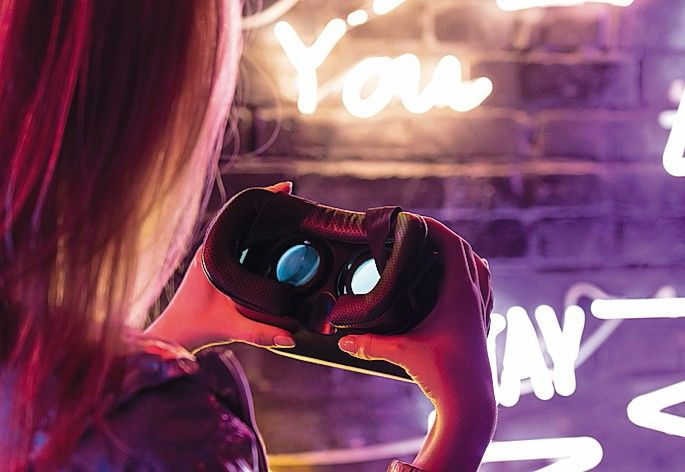 Close_up_view_of_girl_woman_female_hands_holding_vr_headset_glasses_device_illuminated_with_futuristic_purple_neon_lights,_wearable_virtual_augmented_reality_digital_innovation_technology_concept